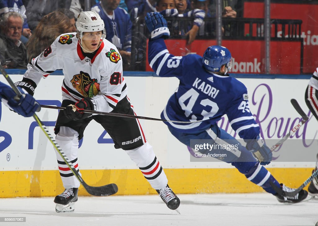 Patrick Kane #88 of the Chicago Blackhawks skates past a falling Nazem Kadri #43 of the Toronto Maple Leafs in an NHL game at the Air Canada Centre on October 9, 2017 in Toronto, Ontario. The Maple Leafs defeated the Blackhawks 4-3 in overtime