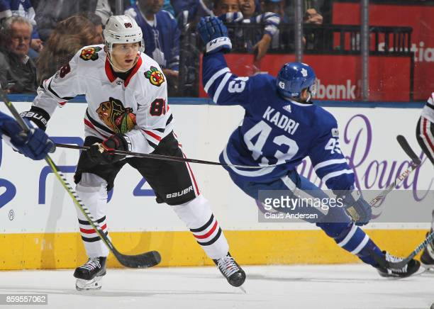 Patrick Kane of the Chicago Blackhawks skates past a falling Nazem Kadri of the Toronto Maple Leafs in an NHL game at the Air Canada Centre on...