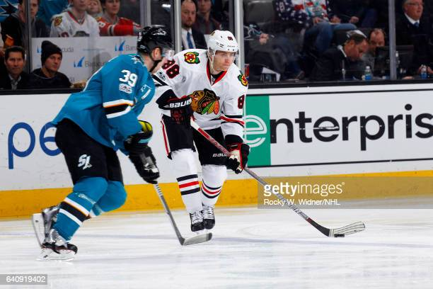 Patrick Kane of the Chicago Blackhawks skates with the puck against Logan Couture of the San Jose Sharks at SAP Center on January 31 2017 in San Jose...