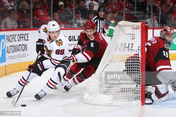 Patrick Kane of the Chicago Blackhawks skates with the puck past Jakob Chychrun and goaltender Darcy Kuemper of the Arizona Coyotes during the third...