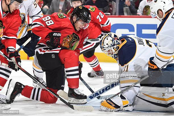 Patrick Kane of the Chicago Blackhawks stops in front of goalie Chad Johnson of the Buffalo Sabres as he gloves the puck in the third period of the...