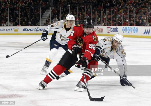 Patrick Kane of the Chicago Blackhawks takes control of the puck as Francis Bouillon of the Nashville Predators reaches around and Martin Erat of the...