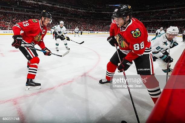 Patrick Kane of the Chicago Blackhawks takes control of the puck ahead of Joonas Donskoi of the San Jose Sharks as Jonathan Toews watches from the...