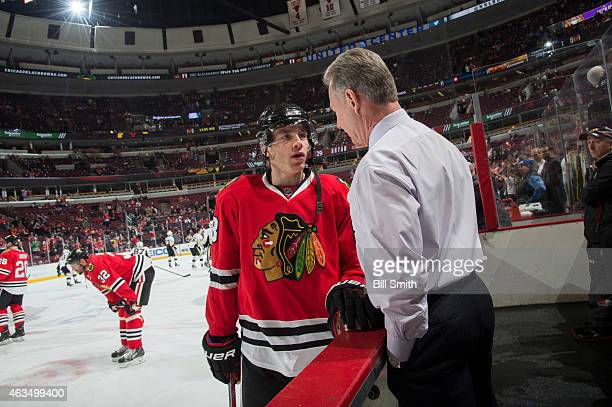 Patrick Kane of the Chicago Blackhawks talks to assistant coach Mike Kitchen prior to the NHL game against the Pittsburgh Penguins at the United...