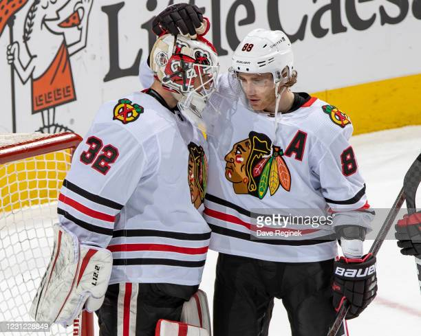 Patrick Kane of the Chicago Blackhawks taps the helmet of teammate Kevin Lankinen to congratulate him on his shutout after an NHL game against the...