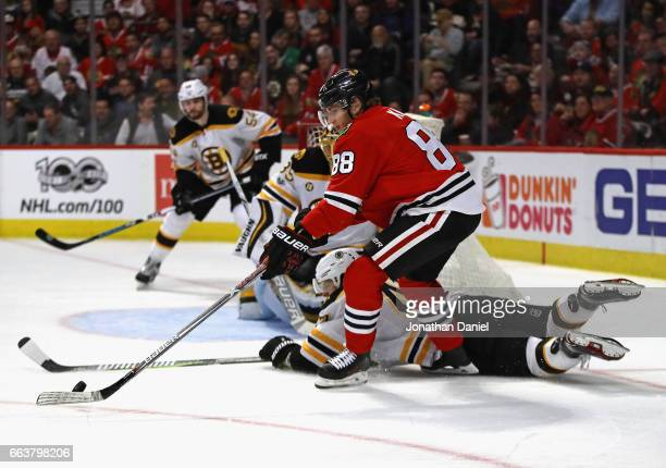 Patrick Kane of the Chicago Blackhawks tries to get off a shot as Torey Krug of the Boston Bruins drops to block in the second period at the United...