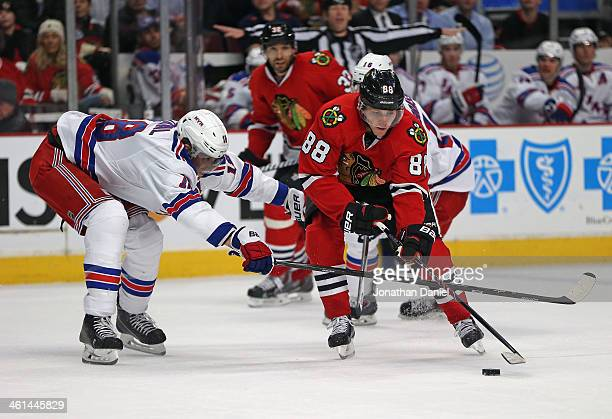 Patrick Kane of the Chicago Blackhawks tries to get off a shot under pressure from Marc Staal of the New York Rangers at the United Center on January...