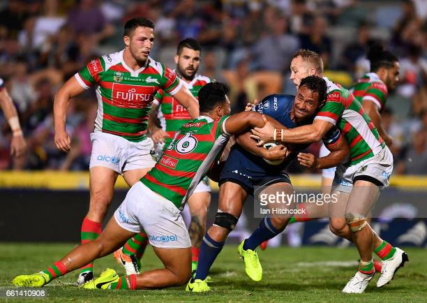 Patrick Kaufusi of the Cowboys is tackled by Zane Musgrove and Jason Clark of the Rabbitohs during the round five NRL match between the North...