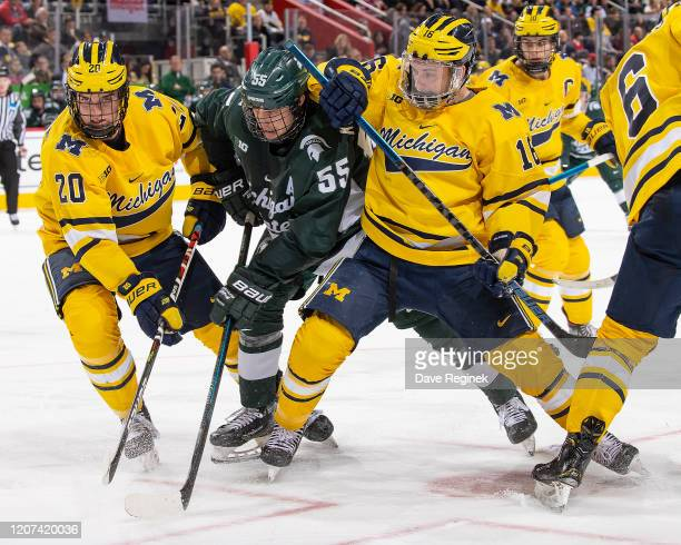 Patrick Khodorenko of the Michigan State Spartans battles for position with Keaton Pehrson and Jacob Hayhurst of the Michigan Wolverines during the...