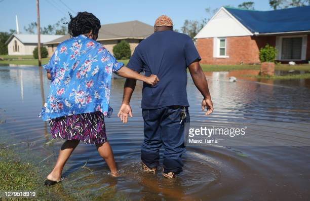 Patrick King and Soncia King walk through flood waters from Hurricane Delta toward their home which they were still repairing from damage from...
