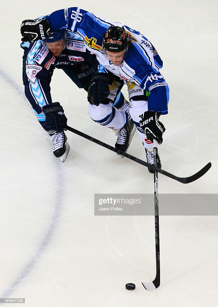 Patrick Koeppchen of Hamburg and Bernhard Keil of Straubing compete for the puck during the DEL game between Hamburg Freezers and Straubing Tigers at O2 World on February 17, 2013 in Hamburg, Germany.