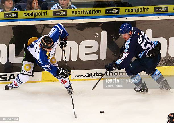 Patrick Koeppchen of Hamburg and Rene Roethke of Straubing compete for the puck during the DEL game between Hamburg Freezers and Straubing Tigers at...