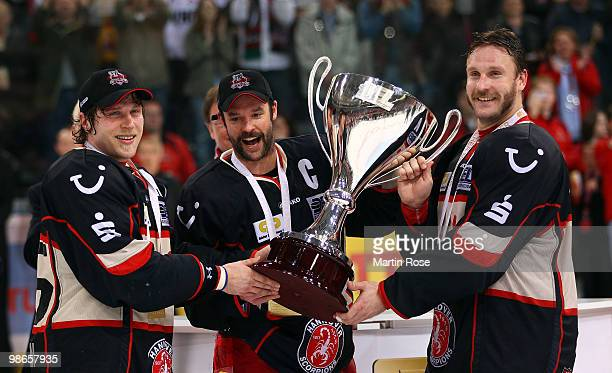 Patrick Koeppchen Tino Boos and Sascha Goc of Hannover celebrate with the trophy after winning the DEL play off final match between Hannover...
