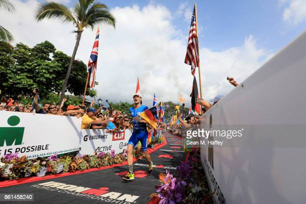 Patrick Lange of Germany celebrates before crossing the finish line to win the IRONMAN World Championship and setting a course record of 80139...