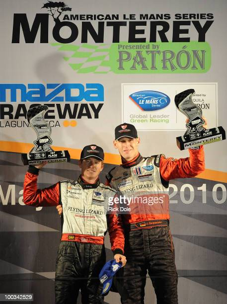 Patrick Long of the USA and Jorg Bergmesiter of Germany drivers of the Flying Lizard Motorsports Porsche celebrate their GT victory during the...