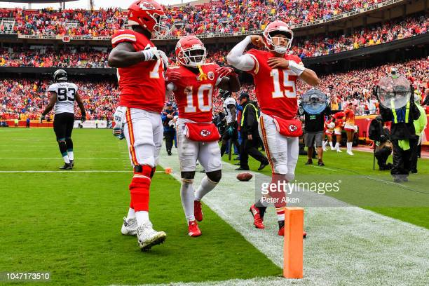 Patrick Mahomes of the Kansas City Chiefs flexes his muscle with teammates Tyreek Hill and Cameron Erving after scoring a rushing touchdown during...