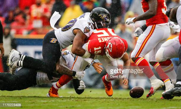 Patrick Mahomes of the Kansas City Chiefs fumbles after being hit by Kenny Young of the Baltimore Ravens on a fourth down play in the third quarter...