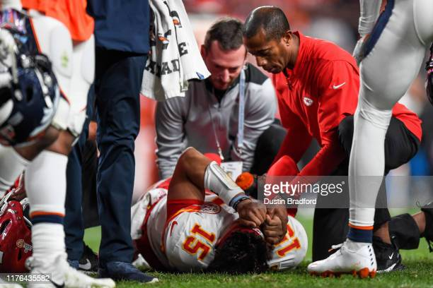 Patrick Mahomes of the Kansas City Chiefs is tended to by trainers after sustaining an injury in the second quarter of a game against the Denver...