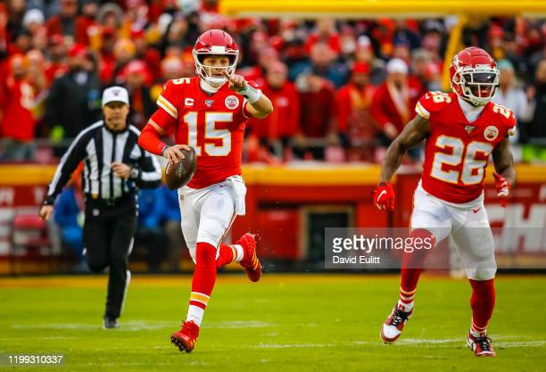 Patrick Mahomes of the Kansas City Chiefs scrambles with Damien Williams of the Kansas City Chiefs during the second quarter of the AFC Divisional...