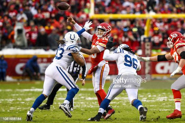 Patrick Mahomes of the Kansas City Chiefs throws a pass under heavy pressure from Denico Autry and teammate Jabaal Sheard of the Indianapolis Colts...
