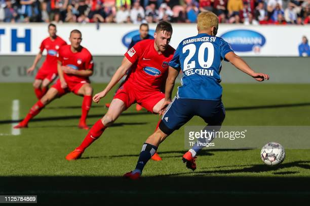 Patrick Mainka of 1 FC Heidenheim 1846 and HeeChan Hwang of Hamburger SV battle for the ball during the Second Bundesliga match between 1 FC...