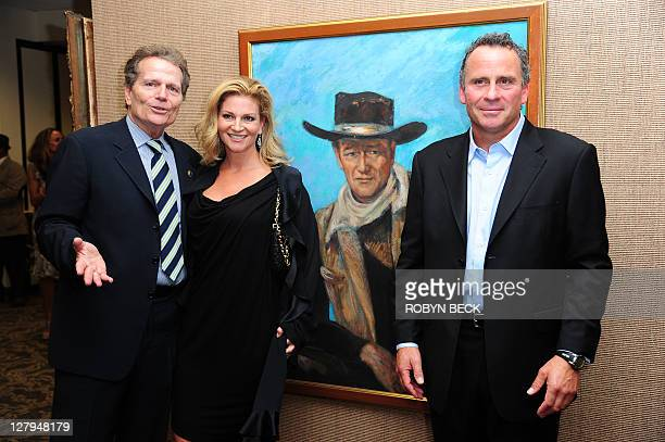 Patrick Marisa and Ethan Wayne children of the iconic American film star John Wayne pose beside a painting of their father at an auction preview...