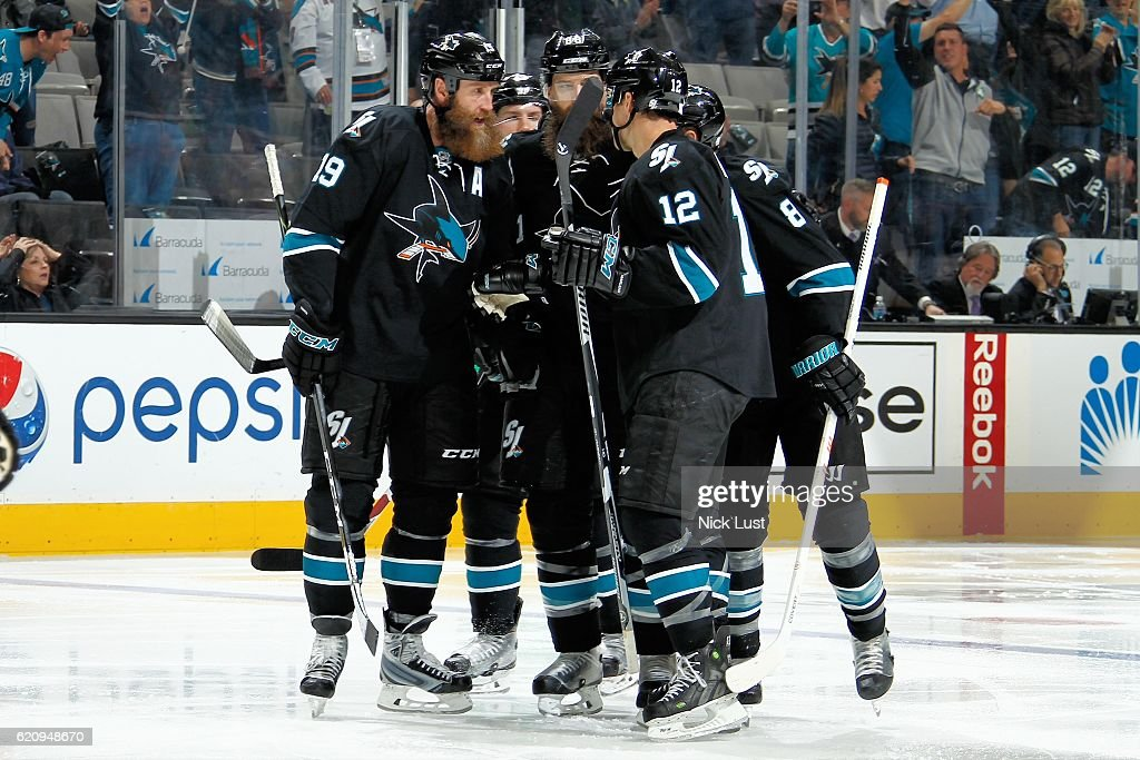 Patrick Marleau #12 and Joe Thornton #19 of the San Jose Sharks celebrate Brent Burn's third period goal with fellow teammates during a NHL game against the Calgary Flames at SAP Center at San Jose on November 3, 2016 in San Jose, California.