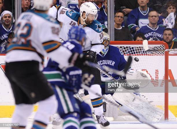 Patrick Marleau of the San Jose Sharks deflects the puck past goaltender Roberto Luongo of the Vancouver Canucks for a goal in the second period in...