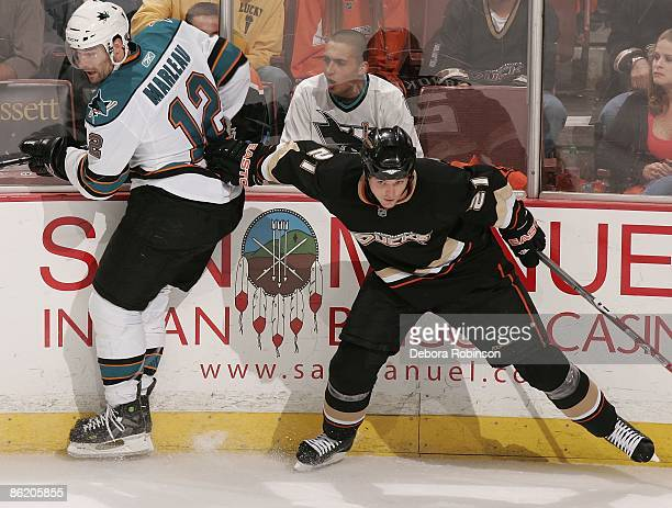 Patrick Marleau of the San Jose Sharks is shoved into the wall by Sheldon Brookbank of the Anaheim Ducks during Game Four of the Western Conference...
