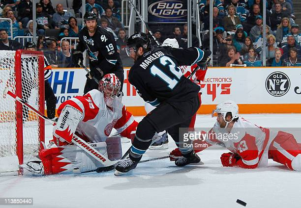 Patrick Marleau of the San Jose Sharks just misses a centering pass from teammate Joe Thornton against Darren Helm and Jimmy Howard of the Detroit...