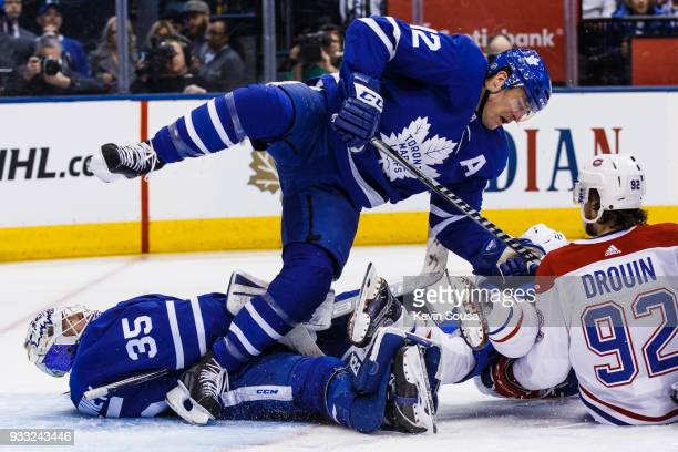 Patrick Marleau of the Toronto Maple Leafs falls over teammate Curtis McElhinney as he battles with Jonathan Drouin of the Montreal Canadiens during...