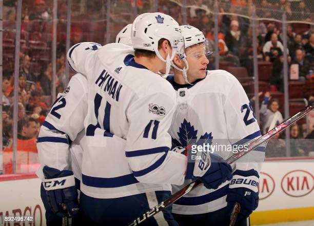 Patrick Marleau of the Toronto Maple Leafs is congratulated by teammates Zach Hyman and Dominic Moore after Marleau scored in the first period...