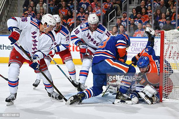 Patrick Maroon and Ryan NugentHopkins of the Edmonton Oilers battle for the puck against Brady Skjei and JT Miller of the New York Rangers on...
