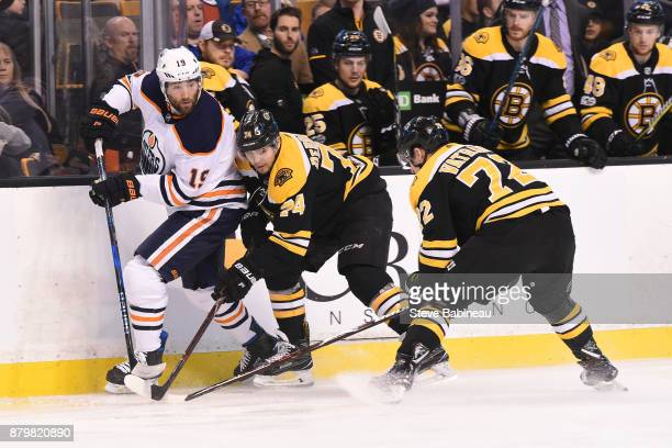 Patrick Maroon of the Edmonton Oilers fights for the puck against Jake DeBrusk and Frank Vatrano of the Boston Bruins at the TD Garden on November 26...
