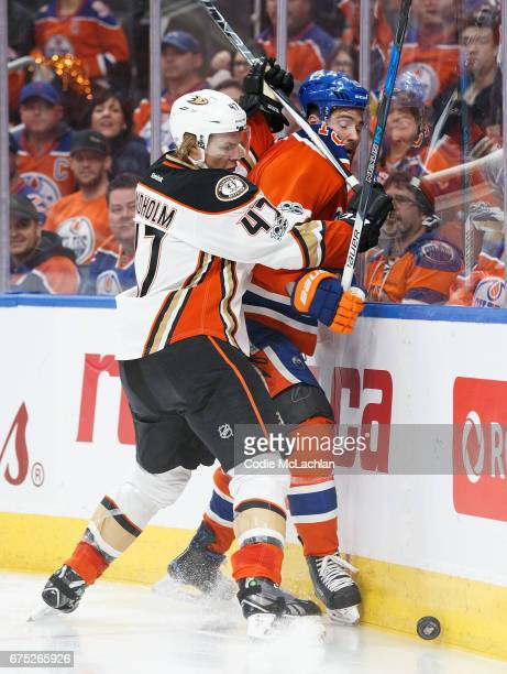 Patrick Maroon of the Edmonton Oilers takes a hit from Hampus Lindholm of the Anaheim Ducks in Game Three of the Western Conference Second Round...