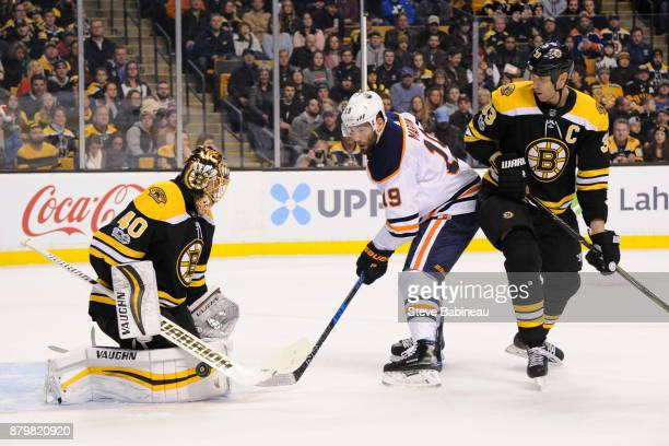 Patrick Maroon of the Edmonton Oilers watches the loose puck against Tuukka Rask and Zdeno Chara of the Boston Bruins at the TD Garden on November 26...