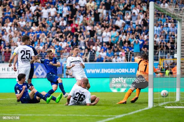 Patrick Mayer of Mannheim scores his team's first goal past goalkeeper Rene Vollath of Uerdingen during the Third League Playoff Leg 2 match between...