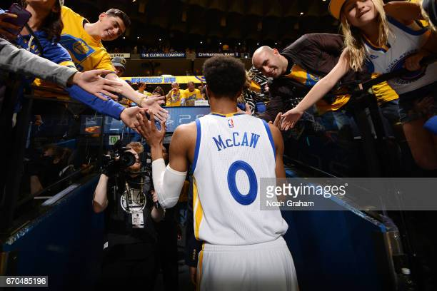 Patrick McCaw of the Golden State Warriors high fives fans as he heads to the locker room after the game against the Portland Trail Blazers during...
