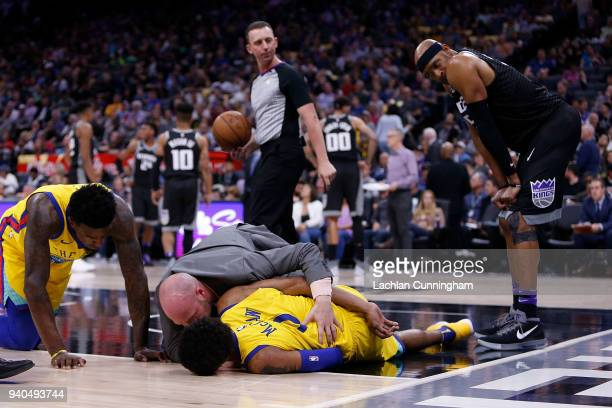 Patrick McCaw of the Golden State Warriors is attended to by team medical staff after being fouled by Vince Carter of the Sacramento Kings at Golden...