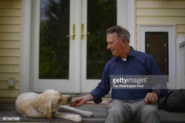 Patrick McNabb who enjoys to play the trombone and works as a IT consultant poses for a portrait photograph with his dog Sonny on the back porch of...