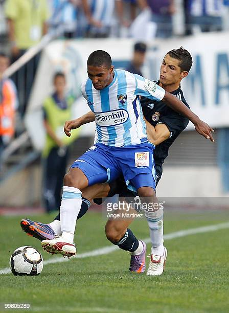 Patrick Mtiliga of Malaga is tackled by Cristiano Ronaldo of Real Madrid during the La Liga match between Malaga and Real Madrid at La Rosaleda...