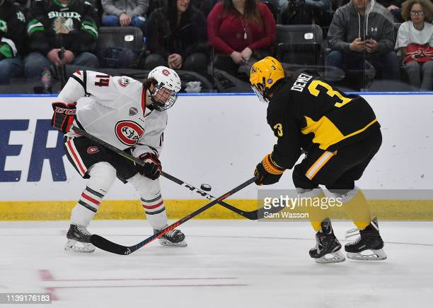 Patrick Newell of the St Cloud State Huskies tries to control the puck against Patrik Demel of the American International Yellow Jackets during an...
