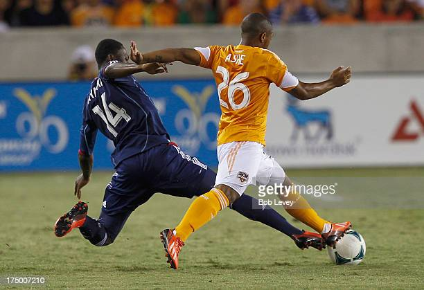 Patrick Nyarko of Chicago Fire attempts to keep the ball away from Corey Ashe of Houston Dynamo at BBVA Compass Stadium on July 27 2013 in Houston...