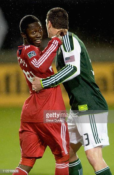 Patrick Nyarko of the Chicago Fire looks for a little help from the referee as he is held by Kenny Cooper of the Portland Timbers during the first...