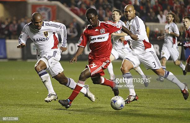 Patrick Nyarko of the Chicago Fire moves the ball as Jamison Olave and Robbie Russell of Real Salt Lake defend during overtime of the MLS Eastern...