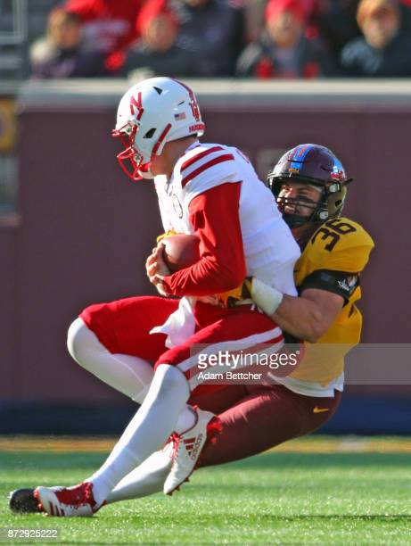 Patrick O'Brien of the Nebraska Cornhuskers gets sacked by Blake Cashman of the Minnesota Golden Gophers in the third quarter against the Minnesota...
