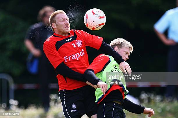 Patrick Ochs jumps for a header with Sascha Wolfert during a training session of Eintracht Frankfurt at Commerzbank Arena on May 10, 2011 in...