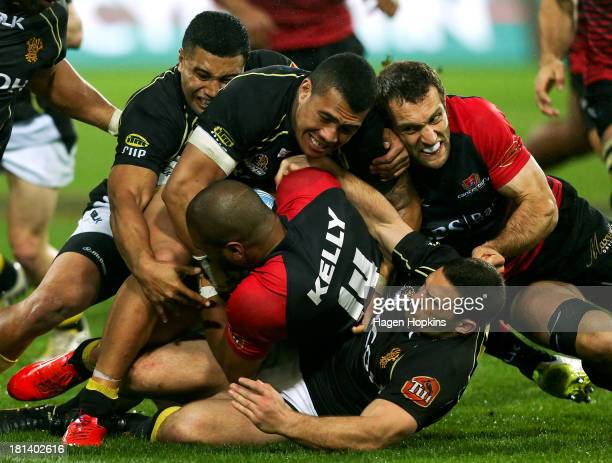 Patrick Osborne of Canterbury with teammate George Whitelock in support is tackled on the Wellington tryline by Lima Sopoaga Ardie Savea and Shaun...