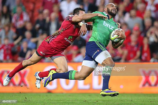 Patrick Osborne of the Highlanders makes a break from Rod Davies of the Reds to score a try of the during the round 16 Super Rugby match between the...