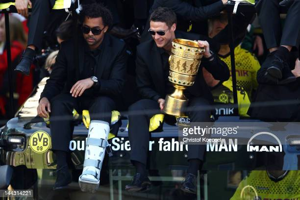 Patrick Owomoyela and Sebastian Kehl sit on the bus with the trophy during a parade at Borsigplatz celebrating Borussia Dortmund's Bundesliga and DFB...